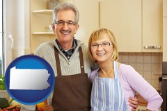 pennsylvania map icon and a senior couple standing in their apartment kitchen