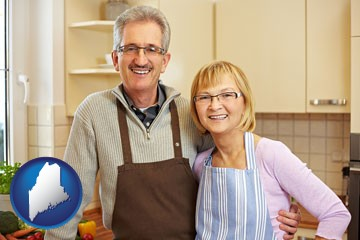 a senior couple standing in their apartment kitchen - with Maine icon